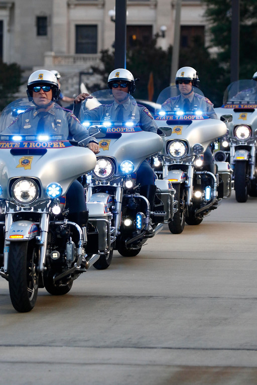 . Motorcycle police from state and local jurisdictions ride past the Statewide Fallen Officers Memorial during the Mississippi Law Enforcement Memorial Candlelight Vigil in Jackson, Miss., Tuesday, May 15, 2018. (AP Photo/Rogelio V. Solis)