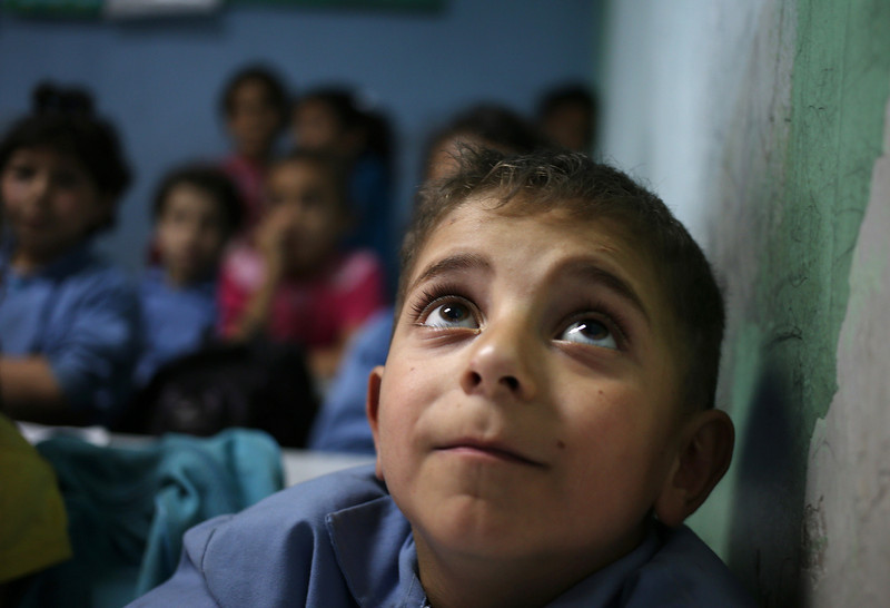 . In this picture taken on Thursday, May 29, 2014, a Syrian refugee boy sits in a classroom at a Lebanese public school where only Syrian students attend classes in the afternoon, in Kaitaa village in north Lebanon. (AP Photo/Hussein Malla)