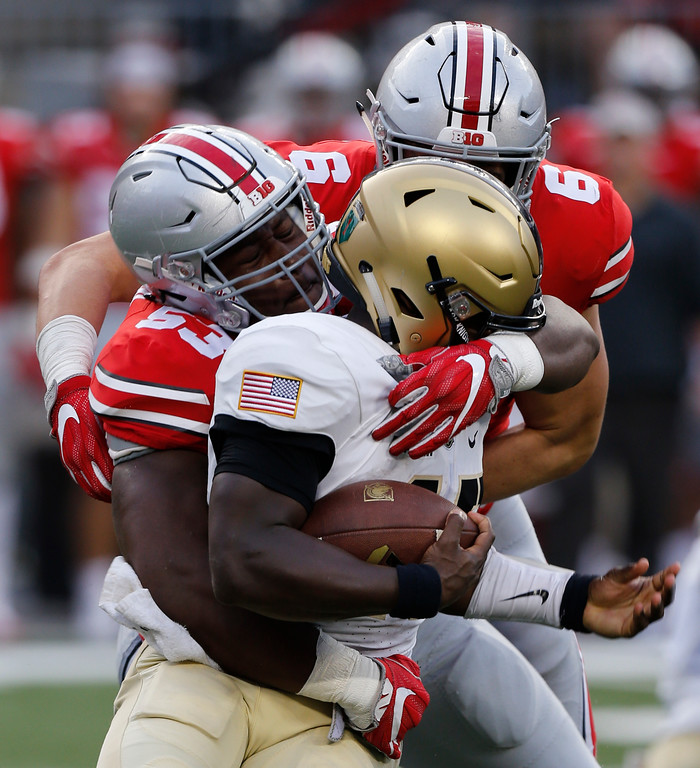 . Army quarterback Ahmed Bradshaw, front, is tackled by Ohio State defenders Davon Hamilton, left, and Sam Hubbard during the second half of an NCAA college football game Saturday, Sept. 16, 2017, in Columbus, Ohio. Ohio State beat Army 38-7. (AP Photo/Jay LaPrete)