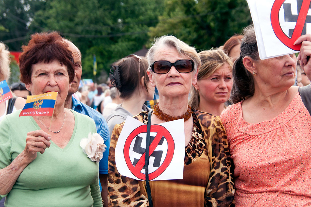 . Women hold placards displaying a crossed swastika during an anti-election rally by pro-Russian supporters in the northeast Ukrainian city of Kharkiv on May 25, 2014. Chocolate baron Petro Poroshenko claimed victory today in Ukraine\'s presidential election, vowing to bring peace after months of turmoil and a pro-Russian insurgency that thwarted voting across much of the separatist east. The 48-year-old self-made billionaire, who exit polls said had won almost 56 percent of the vote, swiftly declared that he would work to bring peace to Ukraine.  AFP PHOTO / SERGEY BOBOKSERGEY BOBOK/AFP/Getty Images