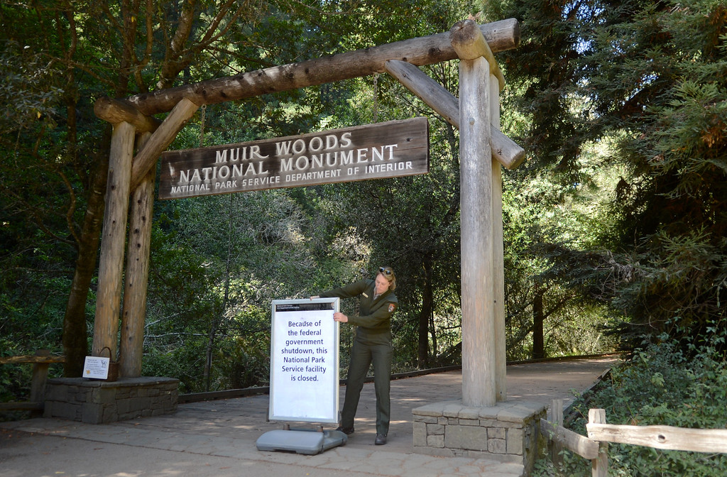 """. Park ranger Sam Bell places a closed sign at the entrance to Muir Woods National Monument in Mill Valley, Calif. on Tuesday, Oct. 1,  2013. The sign reads, \""""Because of the federal government shutdown, this National Park Service facility is closed.\"""" (Alan Dep/Marin Independent Journal)"""