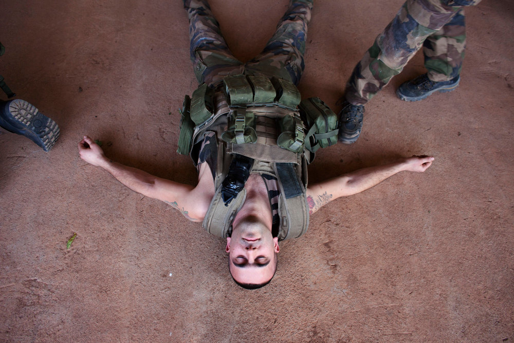 . A French soldier lies on the ground during training for emergency first aid at the Malian army air base in Bamako January 14, 2013. France, which has poured hundreds of troops into the capital Bamako in recent days, carried out more air raids on Monday in the vast desert area seized last year by an Islamist alliance grouping al Qaeda\'s north African wing AQIM alongside Mali\'s home-grown MUJWA and Ansar Dine militant groups. REUTERS/Joe Penney