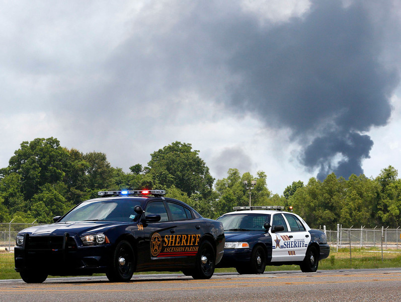 . Smoke rises in the background at a road block near the Williams Olefins chemical plant, after an explosion and fire there, in Geismar, Louisiana June 13, 2013. An explosion and fire tore through the chemical plant on Thursday, injuring 33 people and leading authorities to order people within two miles (3 km) to remain indoors. REUTERS/Jonathan Bachman