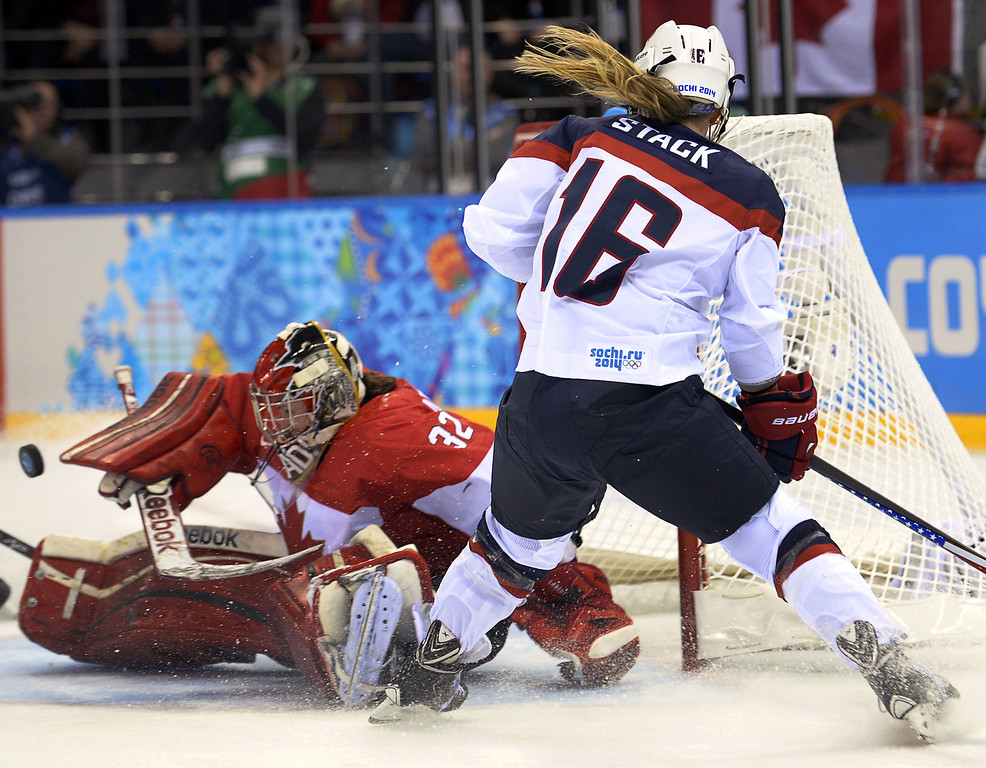. Canada\'s goalkeeper Charline Labonte (L) stops the puck in front of US Kelli Stack during the Women\'s Ice Hockey Group A match between Canada and USA at the Sochi Winter Olympics on February 12, 2014 at the Shayba Arena. AFP PHOTO / ALEXANDER NEMENOV/AFP/Getty Images