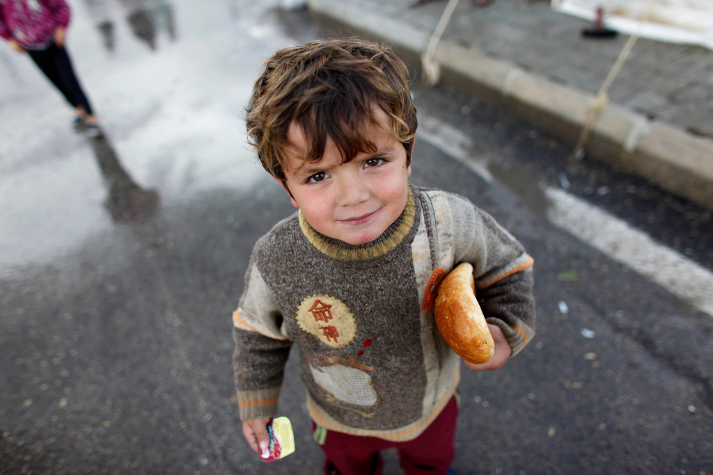 . A Syrian refugee boy holds bread at the Boynuyogun refugee camp on the Turkish-Syrian border in Hatay province February 8, 2012.REUTERS/Murad Sezer