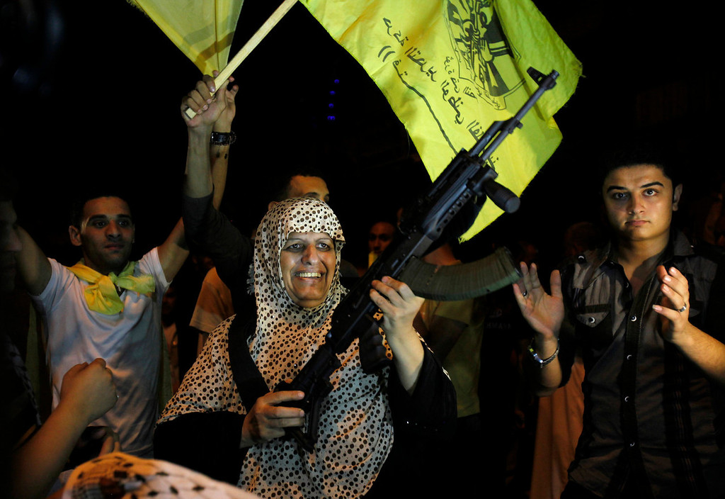". A Palestinian woman dances with a rifle while celebrating the release of Nehad Jondiya, unseen, upon his arrival to his family house in Gaza City, Wednesday, Aug. 14, 2013. Israel released 26 Palestinian inmates, including many convicted in grisly killings, on the eve of long-stalled Mideast peace talks, angering families of those slain by the prisoners, who were welcomed as heroes in the West Bank and Gaza. Arabic reads ""Al Asefa, militant group of Fatah\"".   (AP Photo/Adel Hana)"