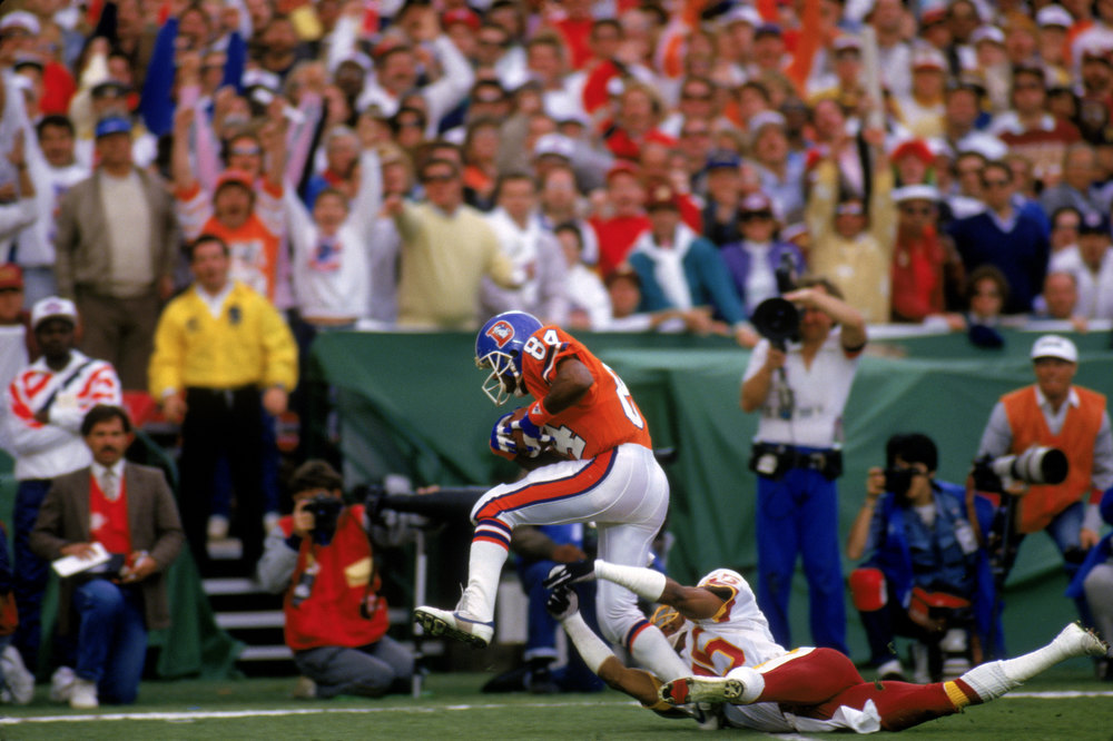 Description of . Wide receiver Ricky Nattiel #84 of the Denver Broncos break away from a tackle by cornerback Barry Wilburn #45 of the Washington Redskins in route to the end zone during Super Bowl XXII at the Jack Murphy Stadium on January 31, 1988 in San Diego, California.  The Redskins won 42-10.  (Photo by George Rose/Getty Images)