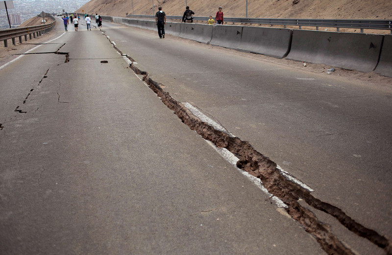 . People walk along a road damaged by a powerful 8.2-magnitude earthquake that hit off Chile\'s Pacific coast, in Iquique, northern Chile, on April 2, 2014. An 8.2-magnitude earthquake hit Chile late Tuesday, killing at least six people and generating tsunami waves that might ripple as far as Indonesia. (JUAN LEONEL/AFP/Getty Images)