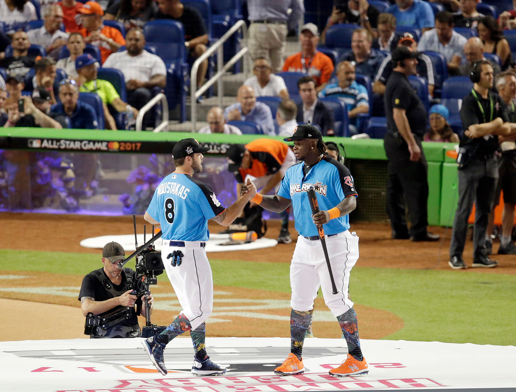 . Kansas City Royals\' Mike Moustakas, left, and Minnesota Twins\' Miguel Sano, right, exchange greetings during the MLB baseball All-Star Home Run Derby opening ceremony, Monday, July 10, 2017, in Miami. (AP Photo/Lynne Sladky)