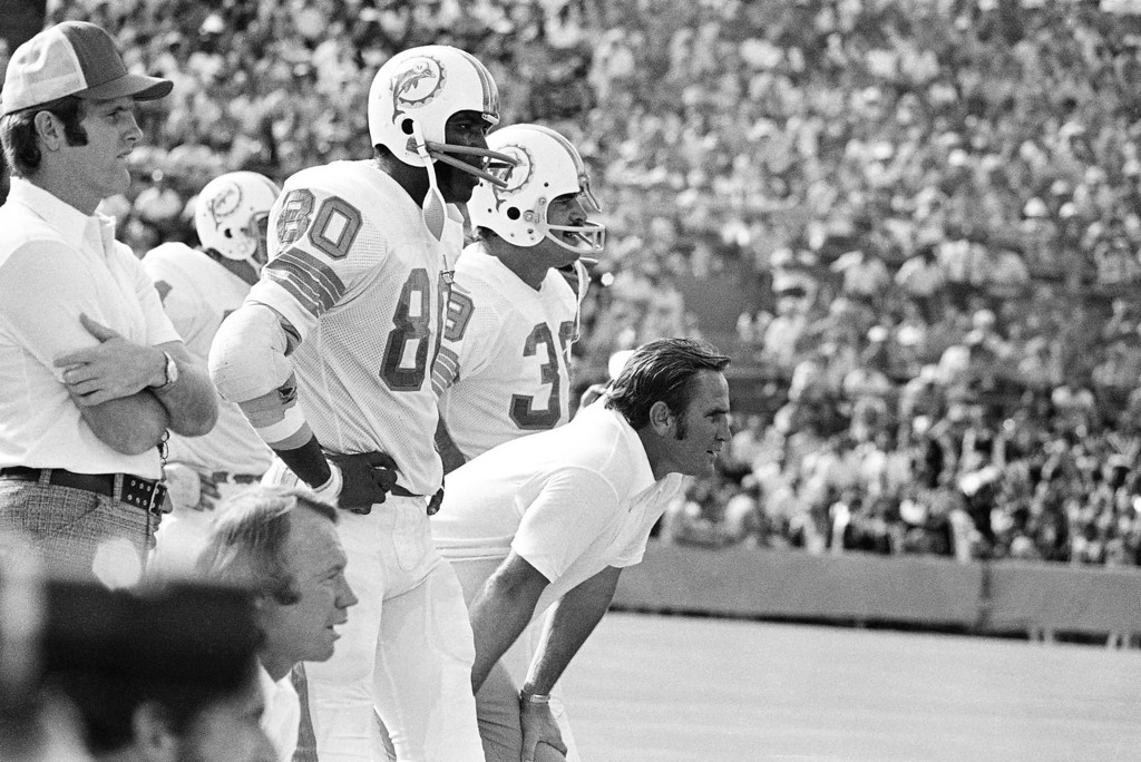 . Miami Dolphin Coach Don Shula leans forward in concentration as he watches his team deliver a 52-0 win over the New England Patriots on Sunday, Nov. 12, 1972 at Miami?s Orange Bowl for his 100th victory. Shula thus became the first NFL coach to win 100 games in his first 10 seasons. With him are Marv Fleming (80) and Larry Csonka (39). (AP Photo/RD)