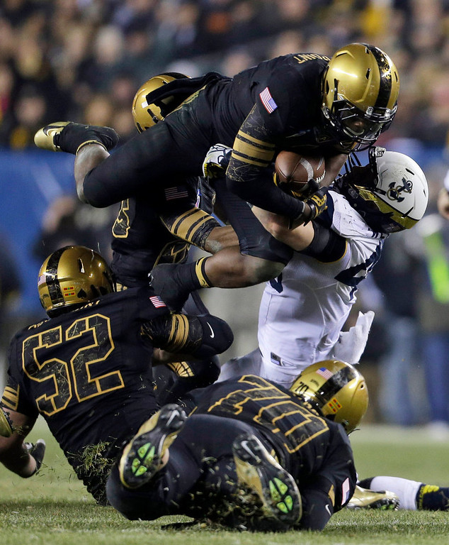 . Army\'s Anthony Stephens, top, is stopped by Navy\'s Keegan Wetzel, during the second half of an NCAA college football game Saturday, Dec. 8, 2012, in Philadelphia. Navy won 17-13. At bottom Ryan Powis (52) and Stephen Shumaker (70).  (AP Photo/Matt Rourke)