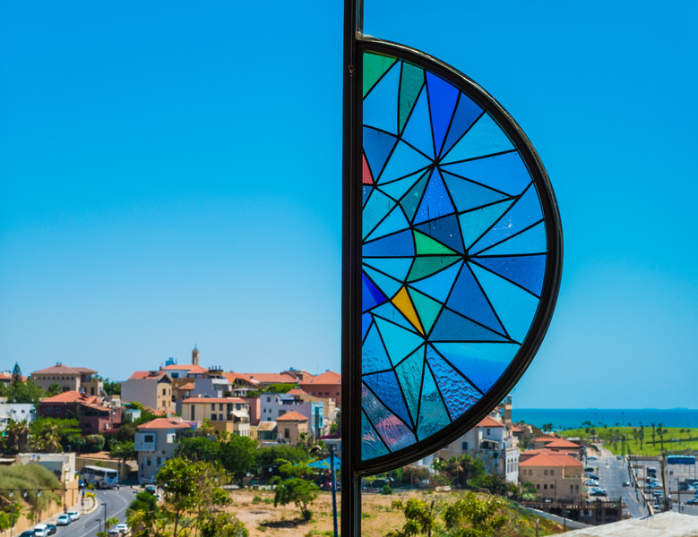 View of Old Jaffa through an open stained glass window