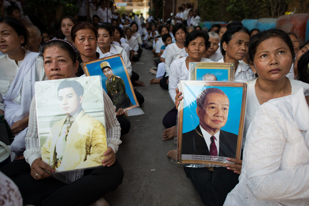 . Cambodian mourners sit in a street in front of the crematorium where a coffin bearing the remains of Cambodia\'s late King Norodom Sihanouk is placed before his cremation, near the Royal Palace in Phnom Penh on February 4, 2013. Thousands of mourners massed in the Cambodian capital as the kingdom cremated its revered former King Norodom Sihanouk, who steered his country through six turbulent decades. AFP PHOTO/ Nicolas  ASFOURI/AFP/Getty Images