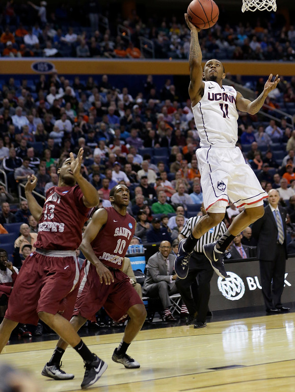 . Connecticut\'s Ryan Boatright (11) drives past Saint Joseph\'s Ronald Roberts Jr. (13) and Langston Galloway (10) during the first half of a second-round game in the NCAA college basketball tournament in Buffalo, N.Y., Thursday, March 20, 2014. (AP Photo/Frank Franklin II)