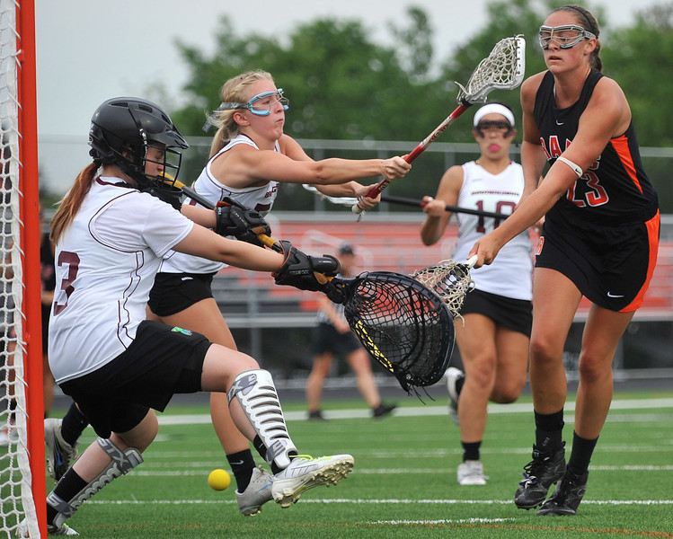 CAPTION INFORMATION Rockford's Meghan Datema shoots through the legs of Birmingham goalie Kaitlyn Pike and scores in the first half of the division 1 state semifinal game in Brighton on June 4, 2014.  (Mark Bialek / Special to the Det News)