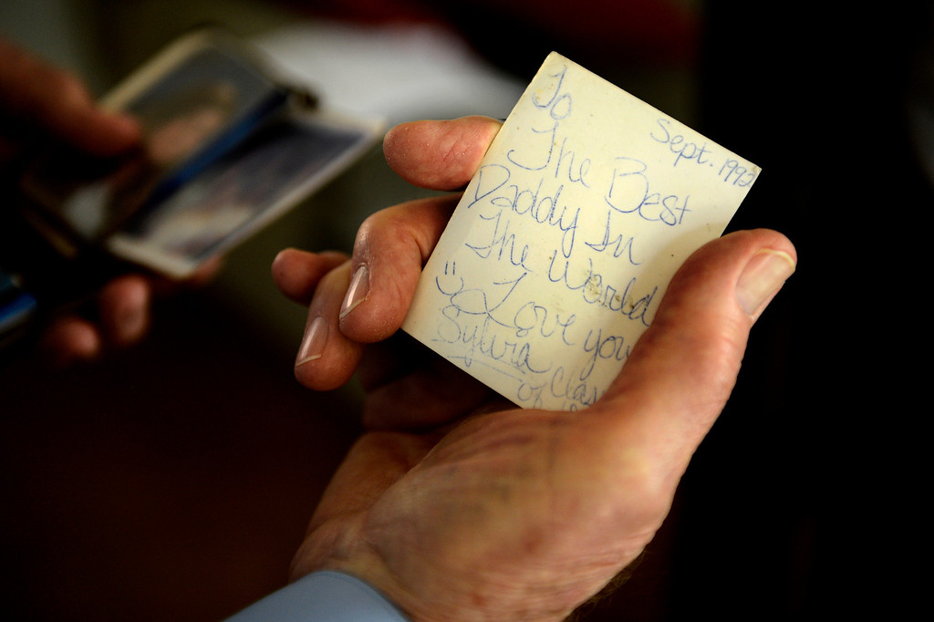 ". AURORA, CO. - May 22: Bob Crowell in his Aurora home holds a photo that has been in his wallet since 1992 with these words on the back, ""To the best daddy in the world, love you Sylvia, class of 93.\"" after he spoke to Governor John Hickenlooper on a conference call with other family members of Nathan Dunlap\'s crimes as the governor announced he granted the death row inmate a \""temporary reprieve\"" from the death penalty May 22, 2013 Aurora, Colorado. (Photo By Joe Amon/The Denver Post)"