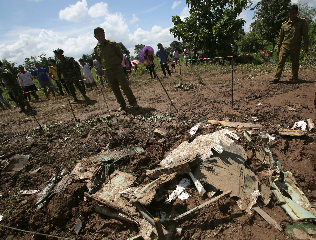 . Lao soldiers and policemen work at the scene where a Lao Airlines turboprop plane hit before skidding into the Mekong River, in Pakse, Laos on Thursday, Oct. 17, 2013.   (AP Photo/Sakchai Lalit)
