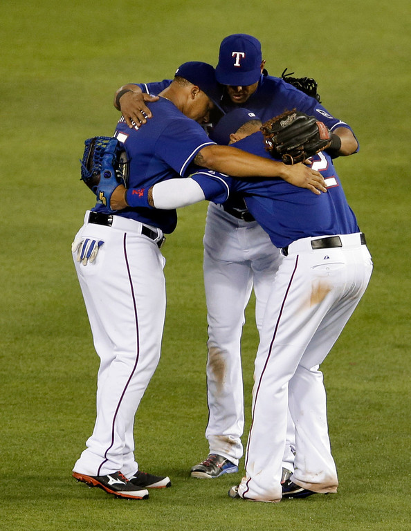 . Texas Rangers\' Michael Choice, left, Leonys Martin (2) and Alex Rios, right, embrace in the outfield as they celebrate their 5-0 win over the Colorado Rockies in a baseball game, Thursday, May 8, 2014, in Arlington, Texas. (AP Photo/Tony Gutierrez)