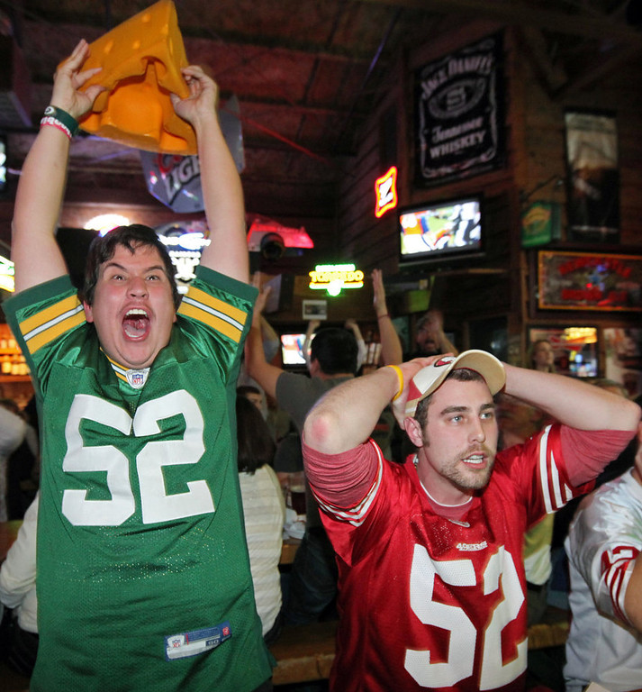 . Greenbay Packers fan Casey Lansdon, left, and San Francisco 49ers fan Ryan Dunn react to a Packers touchdown as they watch a broadcast of an NFC divisional playoff NFL football game on Saturday, Jan. 12, 2013, at The Graduate in Chico, Calif.  (AP Photo/The Chico Enterprise-Record, Jason Halley)