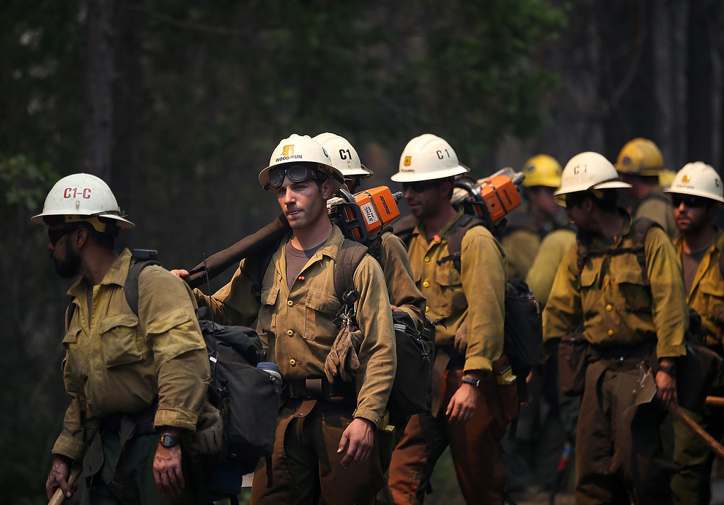 . GROVELAND, CA - AUGUST 22:  U.S. Forest Service firefighters move into position while battling the Rim Fire on August 22, 2013 in Groveland, California. The Rim Fire continues to burn out of control and threatens 2,500 homes outside of Yosemite National Park. Over 1,000 firefighters are battling the blaze that was reduced to only 2 percent containment after it nearly tripled in size overnight.  (Photo by Justin Sullivan/Getty Images)
