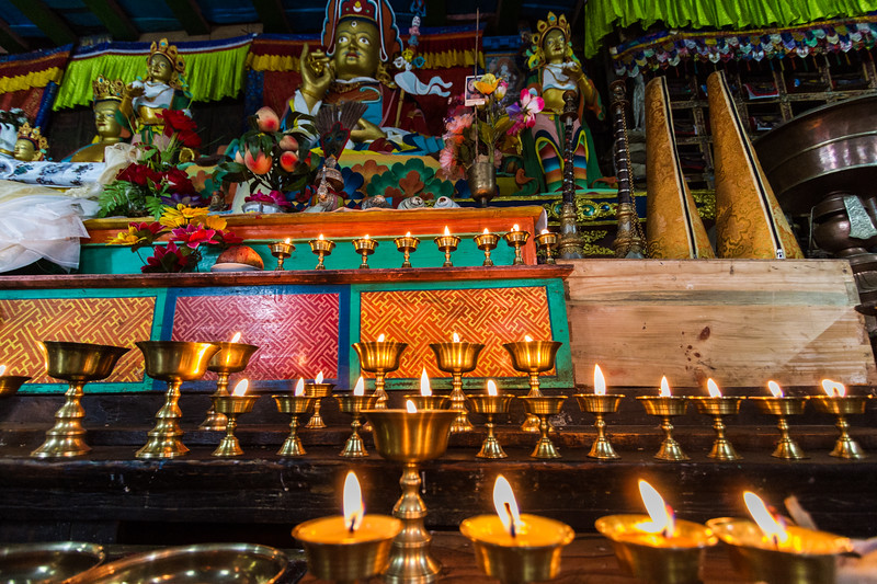Butter candles sit in front of a statue of Guru Rinpoche in teh Khumjung Monastery in Khumjung, Nepal