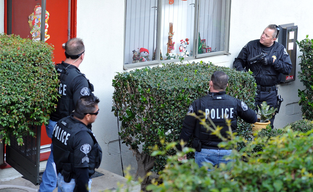 . Whittier Police officers with a task force from area agencies carry out a compliance check at an apartment in Whittier as they look in on local parolees and probationers on Friday morning December 13, 2013. Officers from the multi-agency task force visited 21 homes during the operation. (Staff Photo by Keith Durflinger/San Gabriel Valley Tribune)