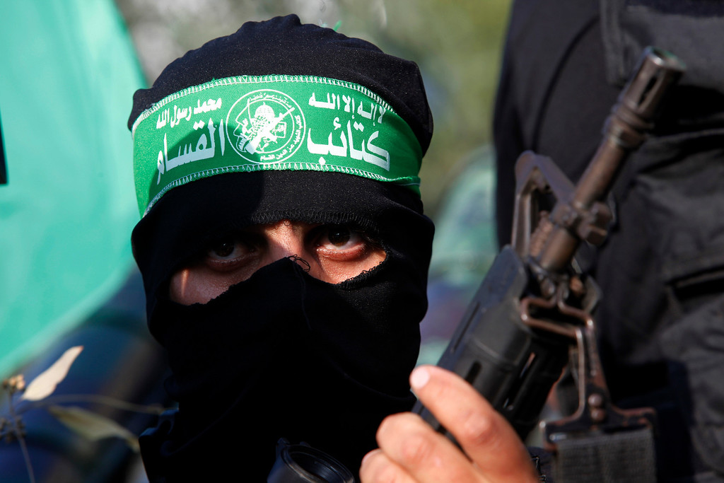 ". A masked Palestinian member of the Ezz Al-Din Al Qassam brigade, the military wing of Hamas, holds his weapon during a parade to mark the anniversary of a battle against Israel in Gaza City, Thursday, Nov. 14, 2013. Israel launched its offensive on Nov. 14, 2012, responding to an upsurge in rocket fire from Hamas-controlled Gaza. The Arabic reads, ""no God but Allah and Muhammad is his messenger. Ezz Al-Din Al Qassam brigade.\"" (AP Photo/Adel Hana)"