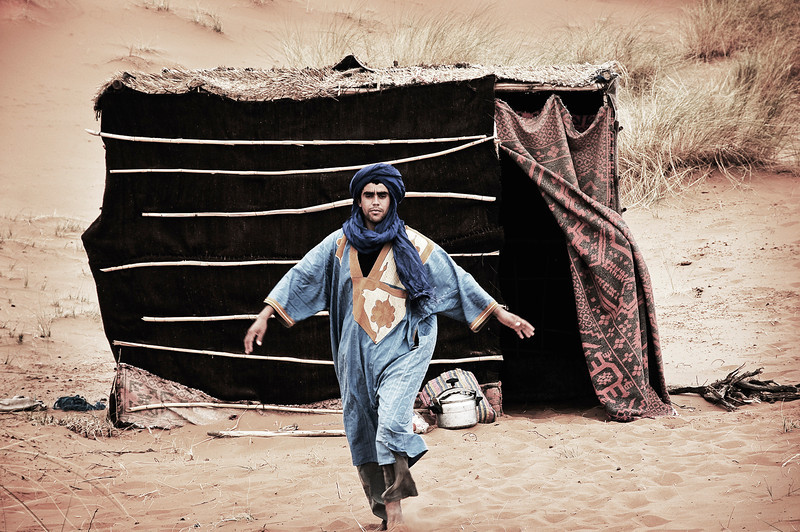 Beduin man coming out of his tent. the blue kaftan and turban is what gives them the nick name, blue men.