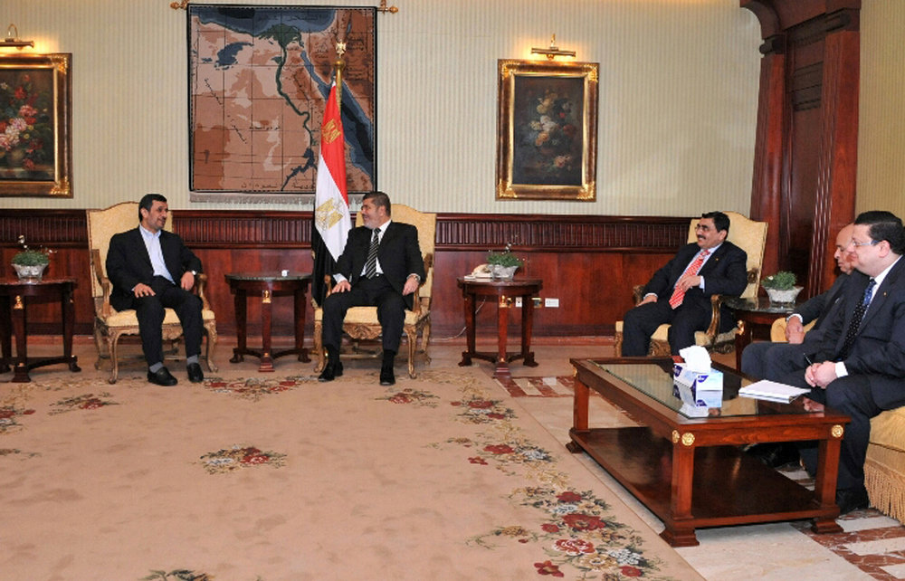 Description of . In this image released by the Egyptian Presidency, Iran's President Mahmoud Ahmadinejad, left, and Egyptian President Mohammed Morsi, center, meet in Cairo, Egypt, Tuesday, Feb. 5, 2013. Ahmadinejad arrived in Cairo on Tuesday for the first visit by an Iranian leader in more than three decades, marking a historic departure from years of frigid ties between the two regional heavyweights.(AP Photo/Egyptian Presidency)