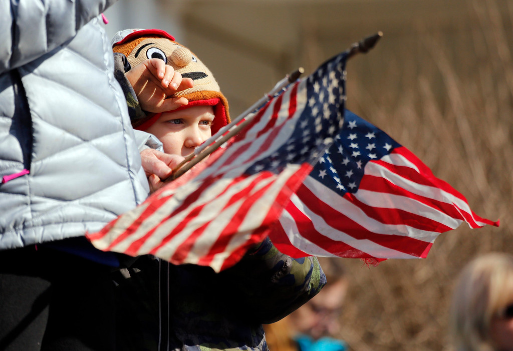 . Jeri Price waves a flag while holding her grandson Price Timmons outside the Hill Funeral Home during a procession transporting the bodies of Westerville Police officers Eric Joering and Anthony Morelli from the Franklin County Coroners Office to the Hill and Moreland funeral homes in Westerville, Ohio, Monday, Feb. 12, 2018. (Adam Cairns/The Columbus Dispatch via AP)