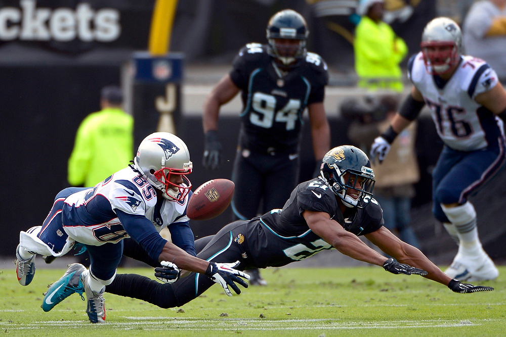 . Jacksonville Jaguars cornerback Derek Cox (21) breaks up a pass intended for New England Patriots wide receiver Brandon Lloyd (85) during the first half of an NFL football game on Sunday, Dec.  23, 2012, in Jacksonville, Fla. (AP Photo/Phelan M. Ebenhack)