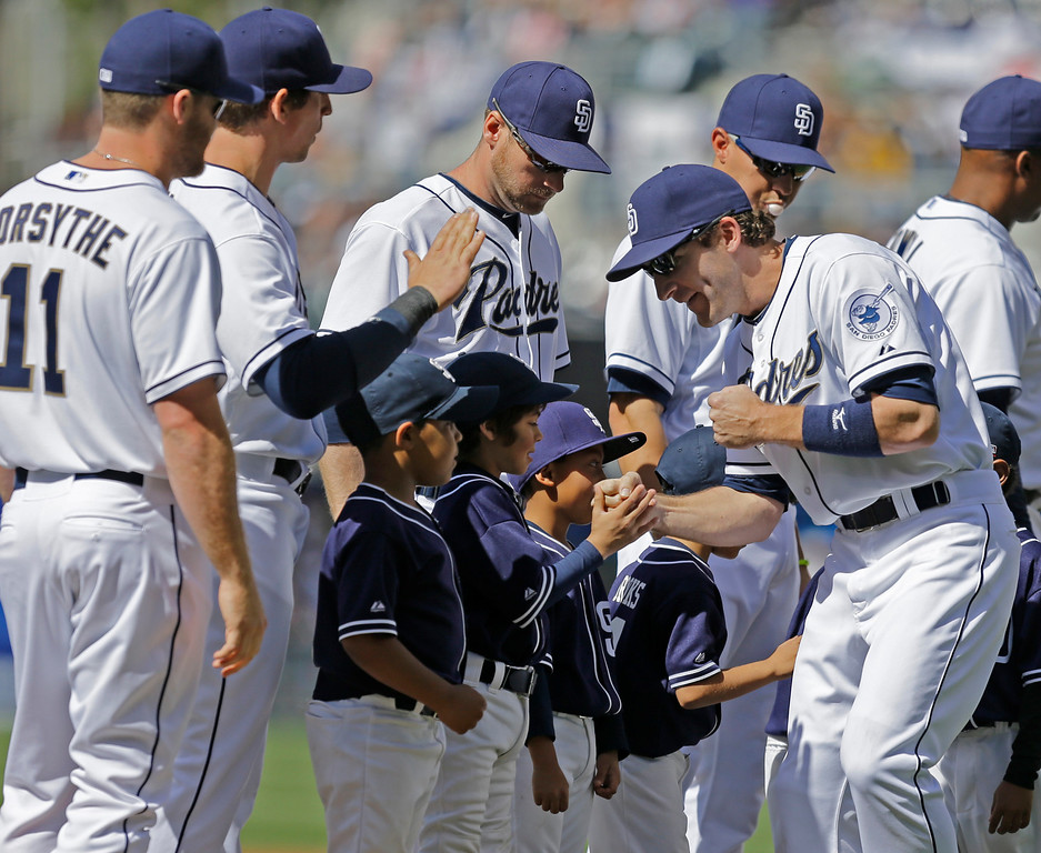 . San Diego Padres\' Chris Denorfia, right, does some knuckle banging with Little Leaguers who accompanied the Padres\' players during team introductions during  their home opener festivities prior to a baseball game against the Los Angeles Dodgers in San Diego, Tuesday, April 9, 2013. (AP Photo/Lenny Ignelzi)