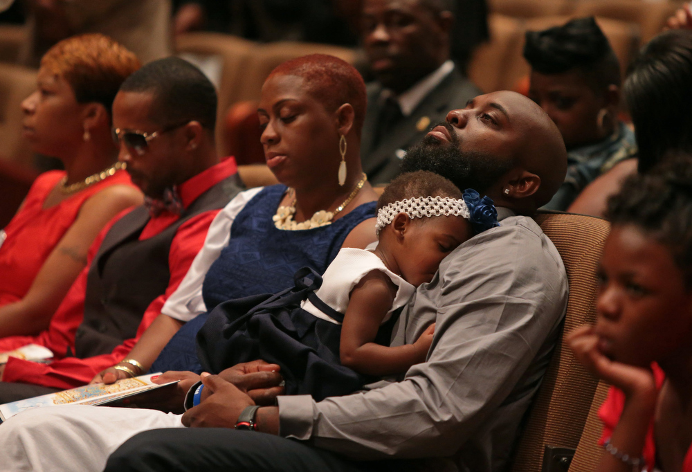 . Michael Brown Sr. sits with an unidentified girl on his lap during the funeral services for his son Michael Brown inside Friendly Temple Missionary Baptist Church on August 25, 2014 in St. Louis Missouri. Also pictured are, from left: Lesley McSpadden, Michael Brown\'s mother; Louis Head, Michael Brown\'s stepfather; and Cal Brown, Michael Brown\'s stepmother. Michael Brown, an 18 year-old unarmed teenager, was shot and killed by Ferguson Police Officer Darren Wilson in the nearby town of Ferguson, Missouri on August 9. His death caused several days of violent protests along with rioting and looting in Ferguson.  (Photo by Robert Cohen-Pool/Getty Images)
