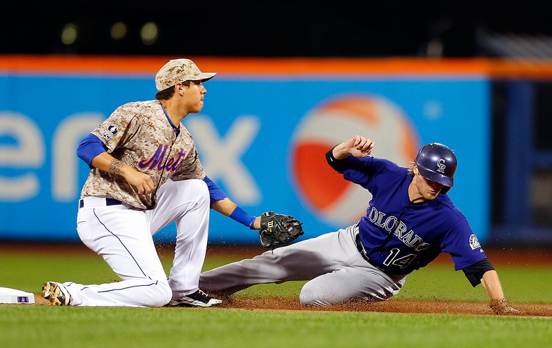 . Josh Rutledge #14 of the Colorado Rockies is caught stealing second base by Wilmer Flores #4 of the New York Mets to end the first inning at Citi Field on September 8, 2014 in the Flushing neighborhood of the Queens borough of New York City.  (Photo by Jim McIsaac/Getty Images)