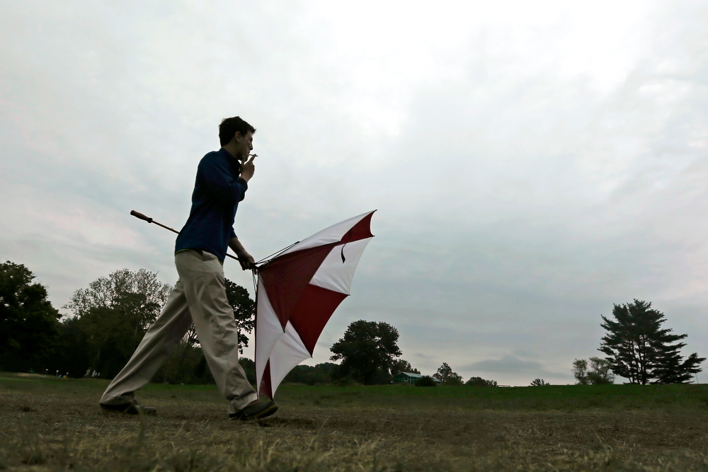 . A spectator walks off the course as a weather warning delays the first round of the U.S. Open golf tournament at Merion Golf Club, Thursday, June 13, 2013, in Ardmore, Pa. (AP Photo/Charlie Riedel)