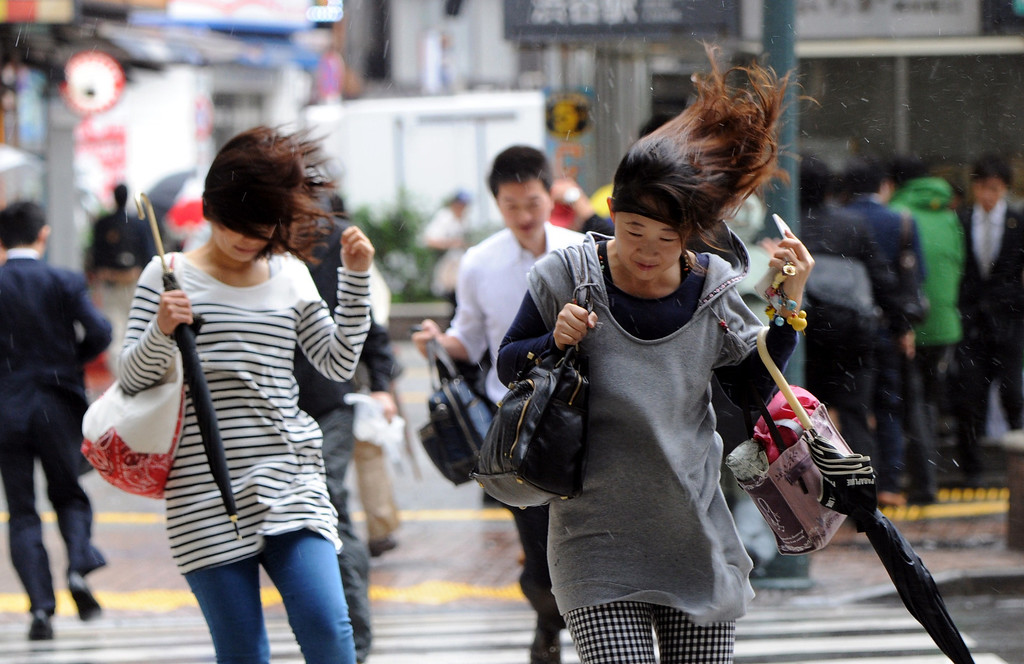 ". People walk against strong wind and rain in Tokyo on October 16, 2013. At least three people died as Typhoon Wipha, the ""strongest in 10 years\"", passed close to Tokyo, causing landslides that swallowed houses on a Japanese island.  AFP PHOTO / Yoshikazu TSUNO/AFP/Getty Images"