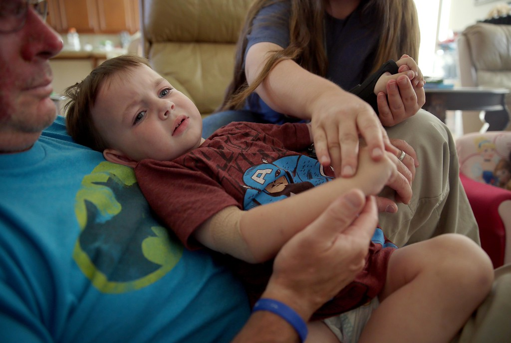. Matthew Ouimet, 3, is comforted by his dad Kelly, left, and mom, Kristi, after falling at his home in Antioch, Calif., on Thursday, May 22, 2014. (Jane Tyska/Bay Area News Group)