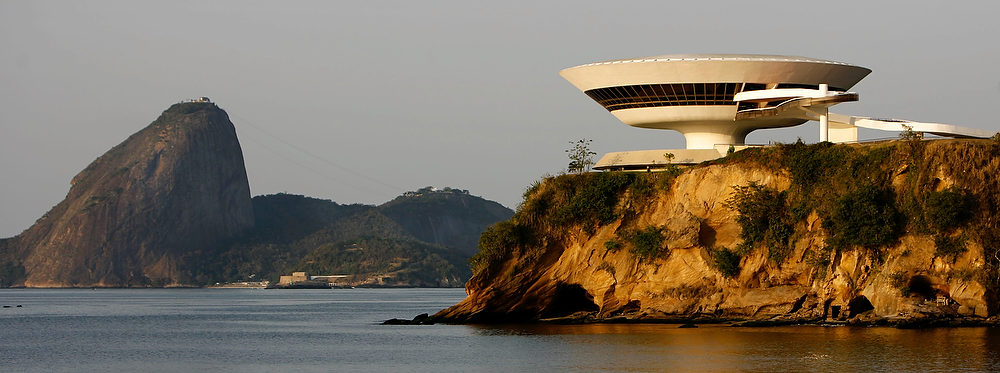 Description of . The Niteroi Contemporary Art Museum, designed by Oscar Niemeyer, overlooks the famed landmark Sugar Loaf, left, in Niteroi, Brazil.  According to a hospital spokeswoman on Wednesday, Dec. 5, 2012, famed Brazilian architect Oscar Niemeyer has died at age 104.  (AP Photo/Ricardo Moraes)