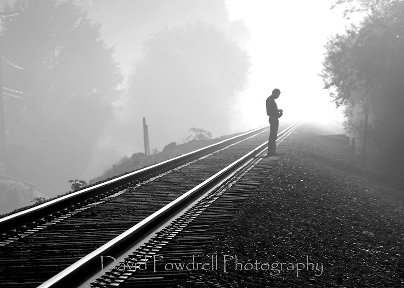 Lone man in the fog at the train tracks