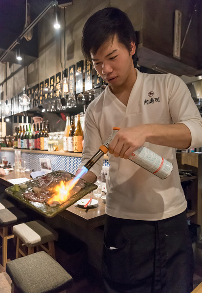 Waiter cooks fresh meat with a blow-torch in a restaurant in Kabukicho, Tokyo, Japan