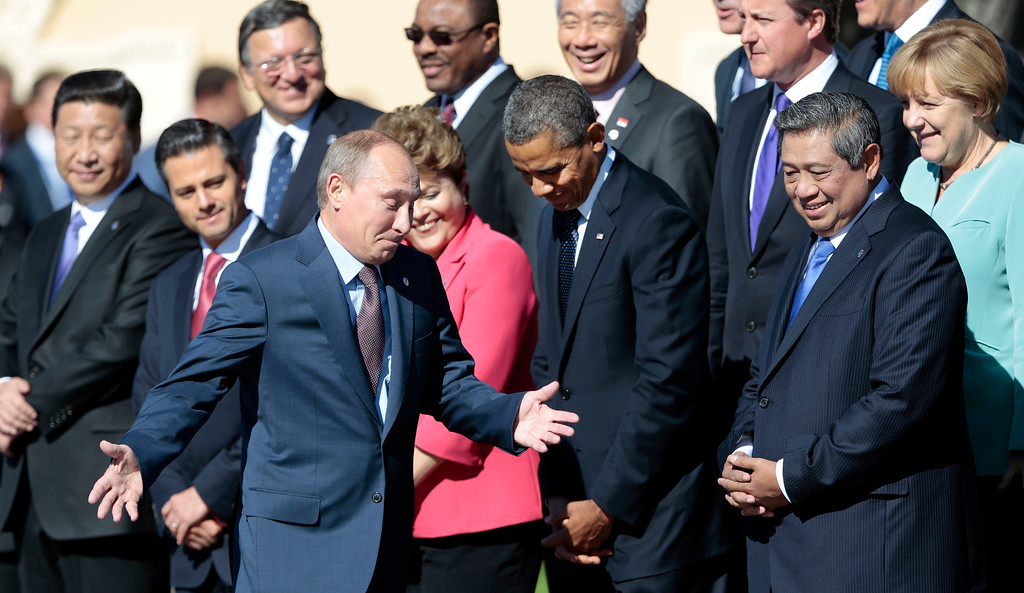 . Russia\'s President Vladimir Putin, center foreground, gestures as he walks by U.S. President Barack Obama, front row second right, as he takes his place at a group photo outside of the Konstantin Palace in St. Petersburg, Russia on Friday, Sept. 6, 2013. World leaders are discussing Syria\'s civil war at the summit but look no closer to agreeing on international military intervention to stop it. (AP Photo/Ivan Sekretarev)