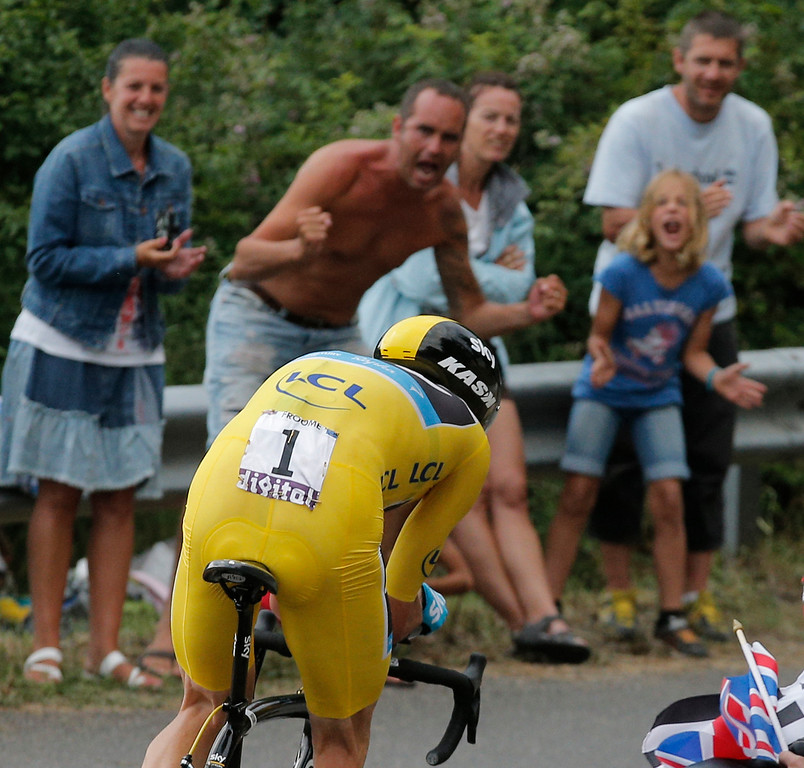 . Spectators cheers as stage winner Christopher Froome of Britain, wearing the overall leader\'s yellow jersey, passes during the seventeenth stage of the Tour de France cycling race an individual time trial over 32 kilometers (20 miles) with start in Embrun and finish in Chorges, France, Wednesday July 17, 2013. (AP Photo/Christophe Ena)