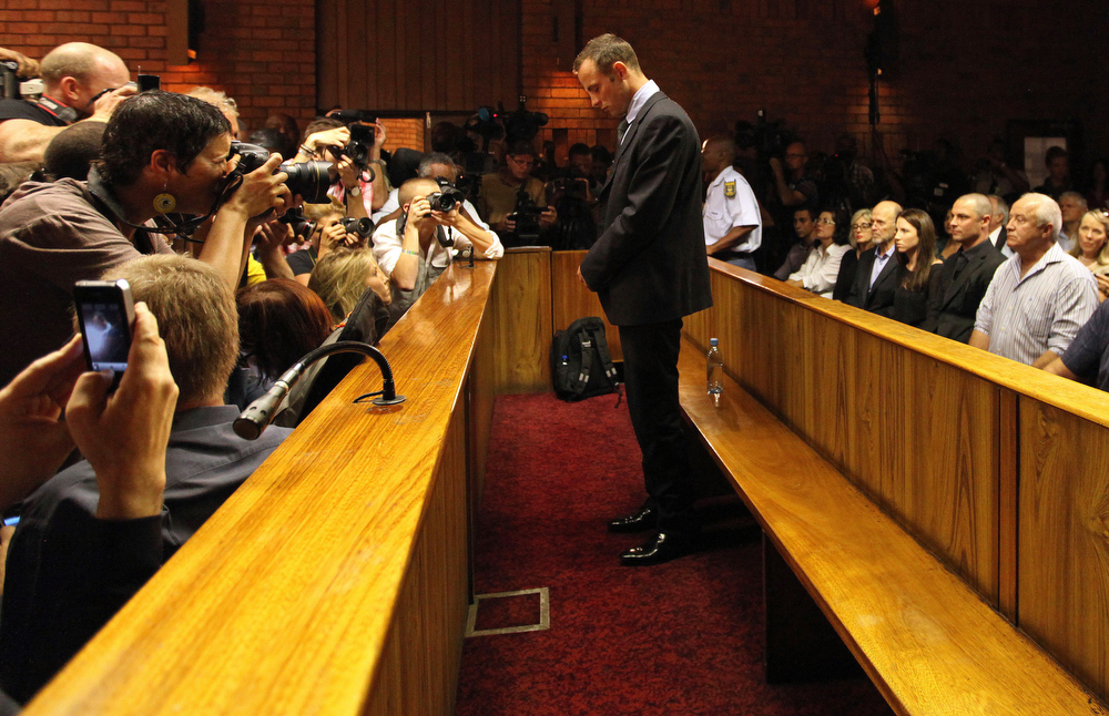 . Olympic athlete Oscar Pistorius stands in the dock during his bail hearing at the magistrates court in Pretoria, South Africa, Friday, Feb. 22, 2013. The fourth and likely final day of Oscar Pistorius\' bail hearing opened on Friday, with the magistrate then to rule if the double-amputee athlete can be freed before trial or if he has to remain in custody over the shooting death of his girlfriend. (AP Photo/Themba Hadebe)