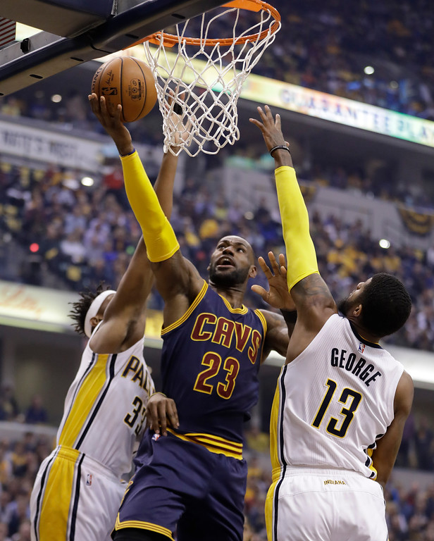 . Cleveland Cavaliers\' LeBron James shoots against Indiana Pacers\' Paul George and Myles Turner during the first half in Game 4 of the first round of the NBA playoffs on April 23 in Indianapolis. The Cavaliers won, 106-102, to sweep the series, 4-0. James led the Cavs in points (33) and assists (4), and Kevin Love led in rebounds (16). (AP Photo/Darron Cummings)