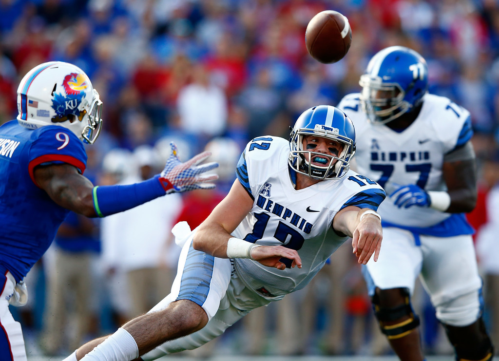 . LAWRENCE, KS - SEPTEMBER 12:  Quarterback Paxton Lynch #12 of the Memphis Tigers releases the ball while scrambling as safety Fish Smithson #9 of the Kansas Jayhawks applies pressure during the game at Memorial Stadium on September 12, 2015 in Lawrence, Kansas.  (Photo by Jamie Squire/Getty Images)