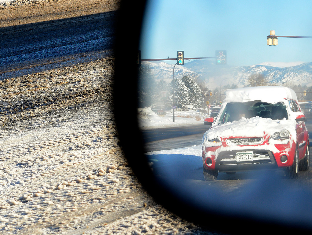 . Roads are covered with ice and snow on west 80th Avenue in Arvada, February, 25, 2013. Road conditions, seen in the refection of a car mirror, in the area made from a long morning commute. (Photo By RJ Sangosti/The Denver Post)