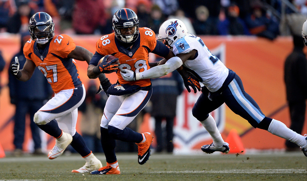 . Denver Broncos wide receiver Demaryius Thomas (88) gets wrapped up by Tennessee Titans cornerback Jason McCourty (30) during the second quarter. (Photo by Hyoung Chang/The Denver Post)