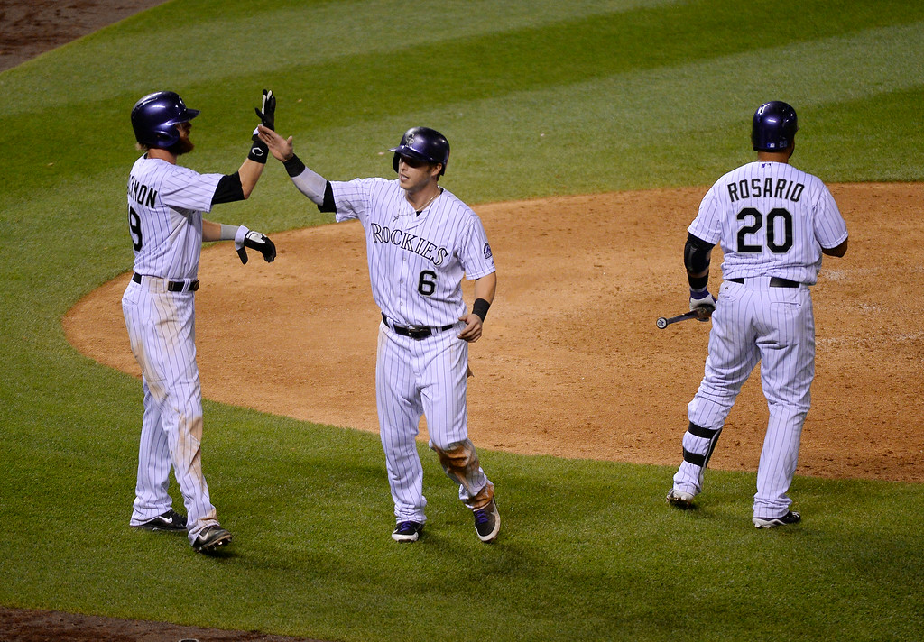 . DENVER, CO - JUNE 24: Colorado Rockies left fielder Corey Dickerson (6) high fives Colorado Rockies center fielder Charlie Blackmon (19) after scoring at home plate on a hit by Colorado Rockies first baseman Justin Morneau (33) in the seventh inning against the St. Louis Cardinals June 24, 2014 at Coors Field. (Photo by John Leyba/The Denver Post)