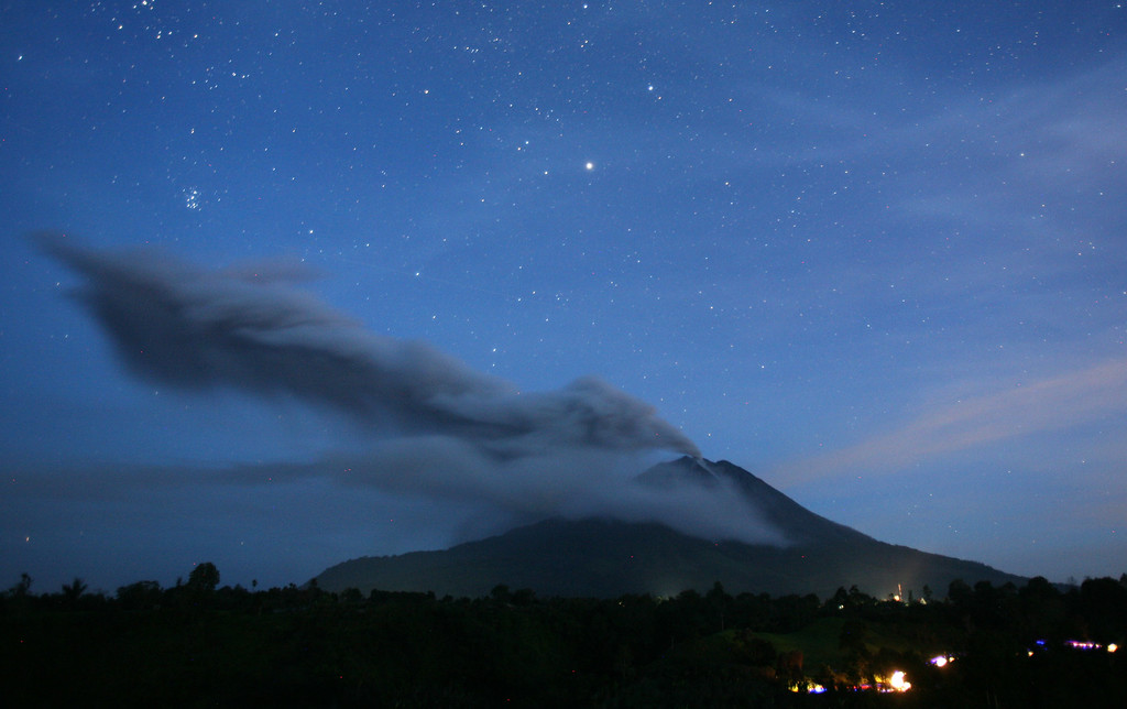 . This picture made with slow shutter speed shows Mount Sinabung spewing volcanic ash as seen from Tiga Pancur, North Sumatra, Indonesia, Tuesday, Nov. 5, 2013.  (AP Photo/Binsar Bakkara)