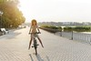young-woman-against-nature-background-with-bike-PTLYQ9T